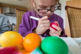 Ein 7 jahre altes Mädchen bemalt ein Osterei - 243550163