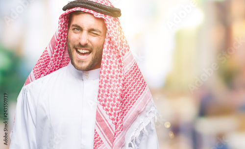 Leinwandbild Motiv Young handsome man wearing keffiyeh over isolated background winking looking at the camera with sexy expression, cheerful and happy face.