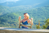 Young pretty blonde woman is standing on the wooden ladder and admires the picturesque landscape. Mountains covered with green forest is seen in a background. Bright sunny day - 243552529