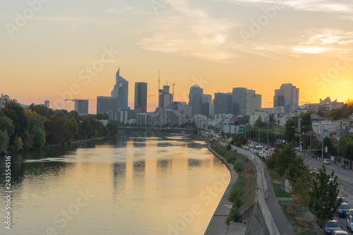 Wall mural Paris, France - 10 15 2018: View of the towers of La Défense district from the Levallois bridge at sunrise