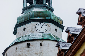 View at Church clock on tower while snow fall in Jelenia Gora, Poland