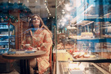 A young woman is sitting behind a window  in a pastry shop cafe with coffee and cake. - 243567931