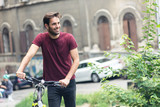 Young handsome man relaxing from his bicycle riding, cycling on the streets - 243573775