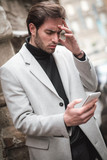 Stressed young fashionable man reading a bad news message on his phone - 243575178