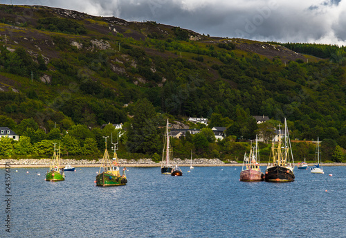 Old Weathered Fishing Boats Anchored In The Harbor Of Ullapool At Loch Broom In Scotland