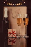Champagne bottle, two wine glasses and gift in a paper bag - 243576729