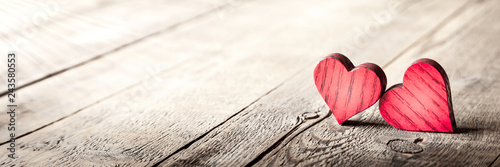 Leinwanddruck Bild Two Rustic Wooden Valentine's Day Hearts On Weathered Wood table With Sunlight