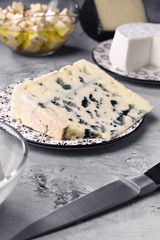 piece of roquefort cheese and other types of cheese on gray marbled background
