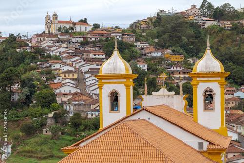 Telhado e torres da igreja Nossa Senhora das Mercês dos Perdões e casario e Igreja de Santa Ifigênia, ao alto, Ouro Preto, Brasil