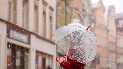 Beautiful adult girl in red coat and scarf with umbrella white snowfall stay on city street © Masson