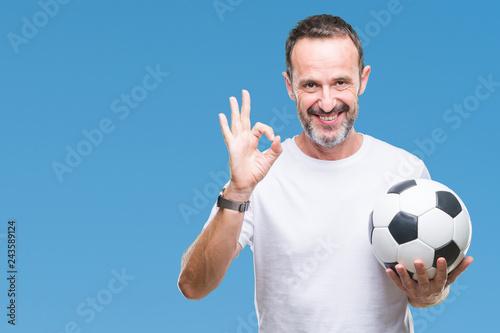 Leinwandbild Motiv Middle age hoary senior man holding soccer football ball over isolated background doing ok sign with fingers, excellent symbol