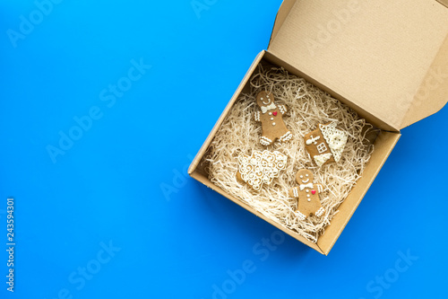 Order goods online concept. Cardboard box with gingerbread cookies on blue background top view space for text