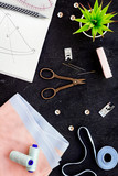 Tailor work place with thread, scissors, fabric. Sewing as hobby. Black background top view - 243594733