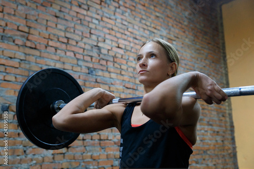 Girl athlete with a barbell. A young girl performs a power exercise with a rod.