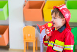 Caucasian boy kid dress up to fireman and use speaker at roll play classroom,Kindergarten preschool education concept.