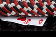 two red poker cards lie under casino chips on a black background