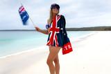 Woman waving Australian flag on beach