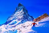 Man skiing on fresh powder snow with Matterhorn in background, Zermatt in Swiss Alps. - 243609769
