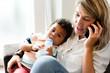 Leinwandbild Motiv Mother feeding her baby while on the phone