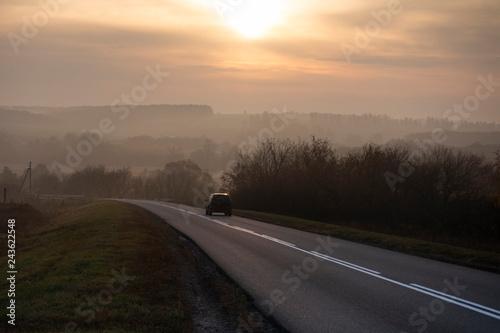 Fridge magnet Car traveling on the asphalt road in a rural autumn landscape at sunset