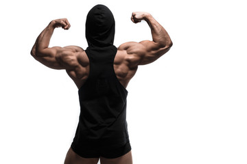 Handsome power athletic man pumping up muscles in anonymous hoodie isolated over white. Strong bodybuilder with perfect shape body and six pack, abs, shoulders, biceps, triceps and wide back. © Fotokvadrat