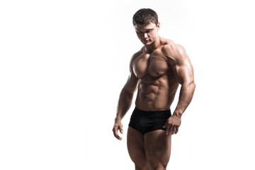 Handsome power athletic man pumping up muscles isolated over white. Strong bodybuilder with perfect shape body and six pack, abs, shoulders, biceps, triceps and chest. © Fotokvadrat