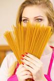 Woman hiding behind long pasta