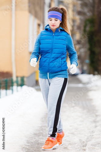 Poster Woman wearing sportswear exercising outside during winter