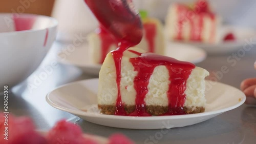 Pouring berry sauce onto slice of cheesecake