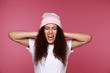 African woman covering ears with her hands, over a pink background