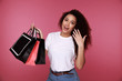Portrait of an excited young african woman holding shopping bags and showing credit card isolated over pink background