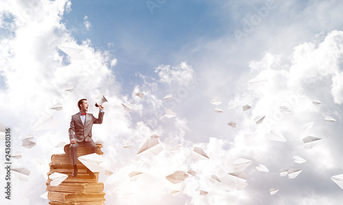 Businessman announcing something in loudspeaker and paper planes fly around © adam121