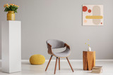 Pile of books next to wooden coffee table with flower in vase and trendy grey chair and yellow pouf