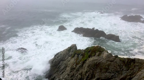 Scenic wide view of Bodega Bay overlooking the rough waves in the ocean crashing against the rocks