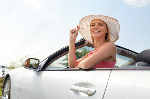 Fridge magnet travel, summer holidays, road trip and people concept - happy young woman wearing hat in convertible car enjoying sun