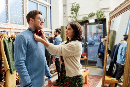 sale, shopping, fashion and people concept - couple choosing bowtie at vintage clothing store