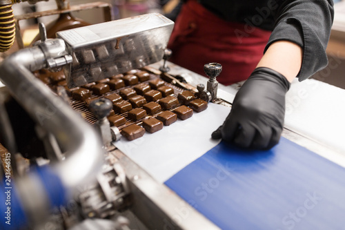 fototapeta na ścianę production, candy shop and people concept - confectioner making candies by chocolate coating machine at confectionery
