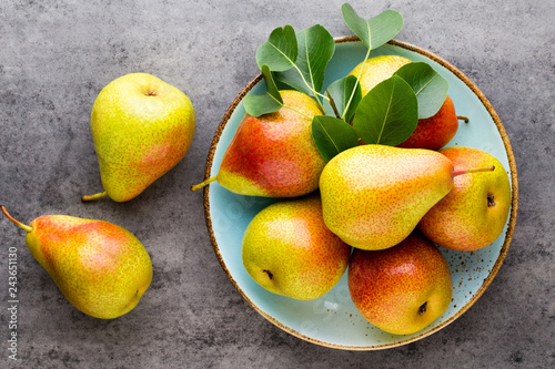 Fresh bio pear with leaves on the plate. Gray stone table.