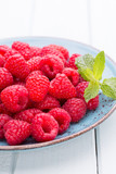 Fresh raspberries in a plate on a  vintage background.