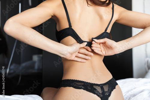 Leinwandbild Motiv Beautiful brunette woman take off her bra lingerie sitting on bed.