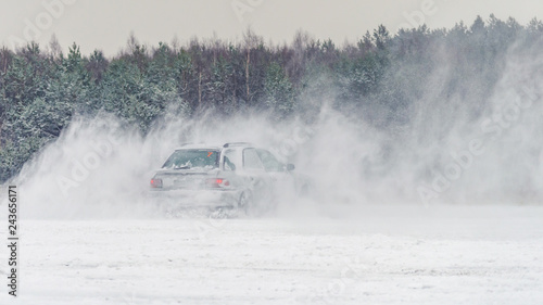 Extreme driving, the car is moving rapidly over the smooth snow and creates a spray of snow. - 243656171