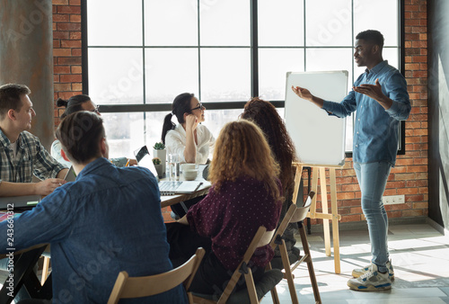 African-american leader lecturing his employees in office
