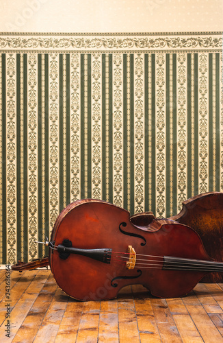Vintage contrabass on wooden floor. Victorian style ornaments on the wall. - 243686364