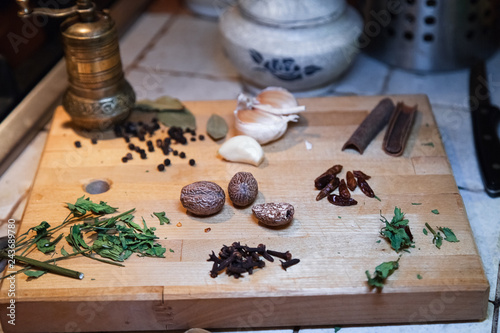 Composition of natural Herbs and spices on wooden cutting board. Rustic kitchen table.Vintage spice grinder.
