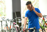 Young Asian man talking on phone when choosing bicycle in store - 243691938