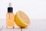 cbd oil in bottle with dropper and half of lemon on wooden surface isolated on white - 243692520