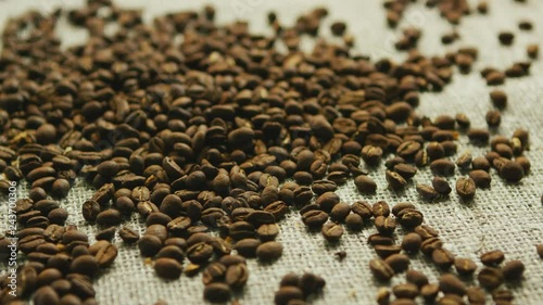 Pile of brown coffee beans laid in mess on textile napkin