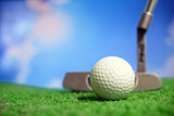 Golf club and golf ball on tee in grass