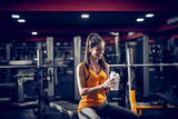 Cute fit young girl sitting in a gym and listening to the music. Relaxing after hard training and drinking water. - 243701310