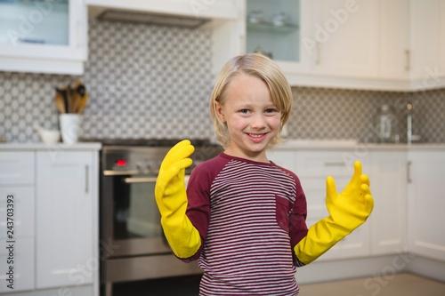 Happy boy in gloves standing in kitchen